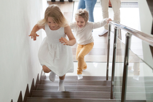 Two children running up the stairs of a home