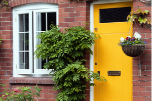 Yellow cottage front door surround by green ivy and hanging baskets