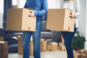 Couple carrying boxes into a new home