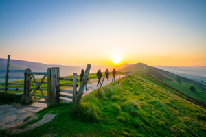 hikers walking along a countryside path at sunrise